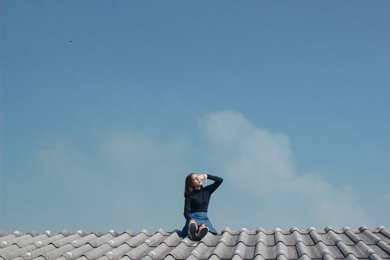 Low angle view of woman on roof against sky