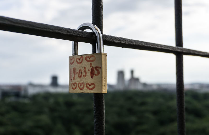 Close-Up Of Date And Heart Shape On Padlock Locked To Metallic Fence Against Sky