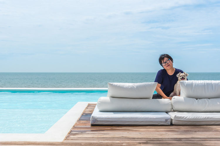 Portrait of woman with dog sitting on pier against infinity pool and sky