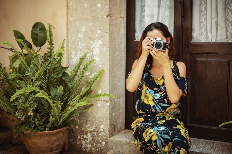 Woman photographing by potted plant against window