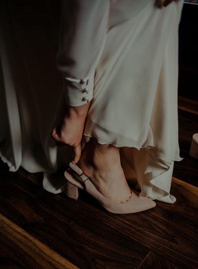 Low section of bride wearing heels on wooden floor