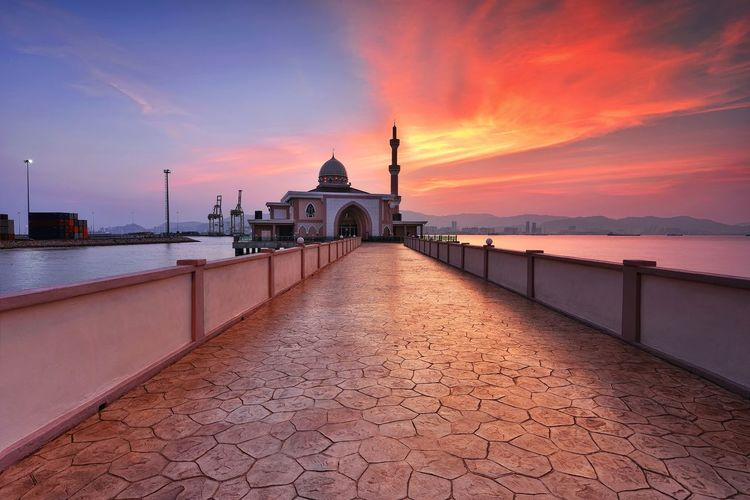 Walkway Leading Towards Mosque By Sea At Sunset Against Sky