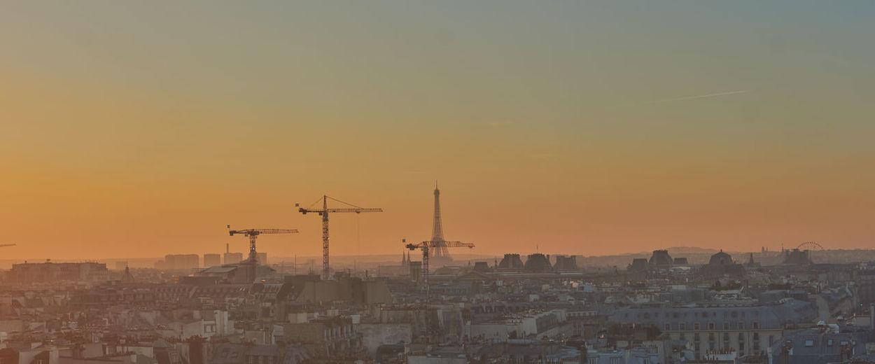 Aerial view of buildings in city against orange sky