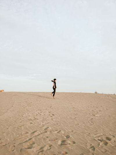 Woman running on beach against sky