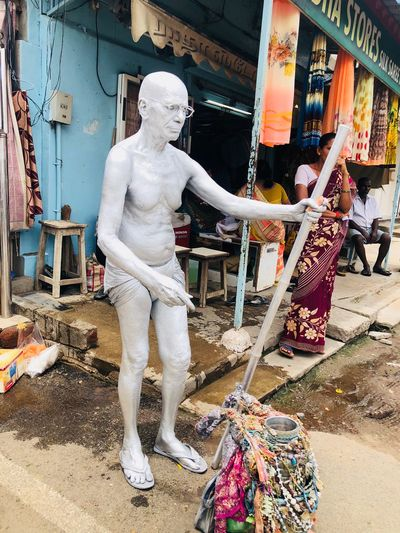 Man working against statue