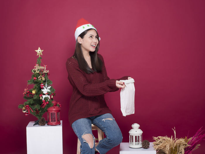 Smiling Young Woman Holding Bag While Sitting Against Red Background During Christmas