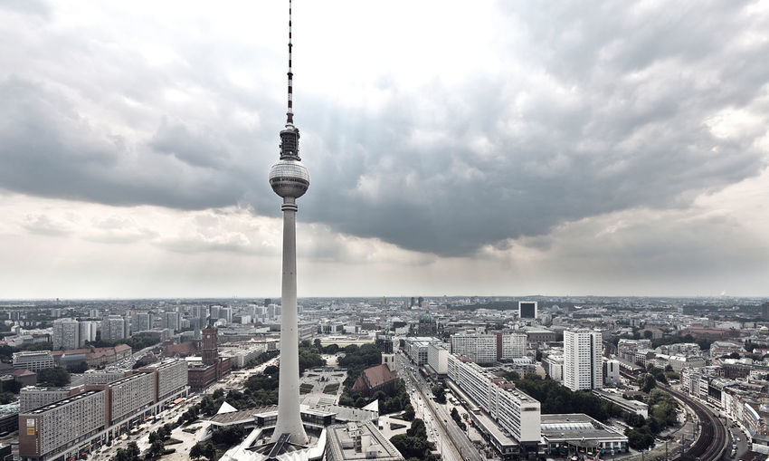 Fernsehturm And Cityscape Against Cloudy Sky