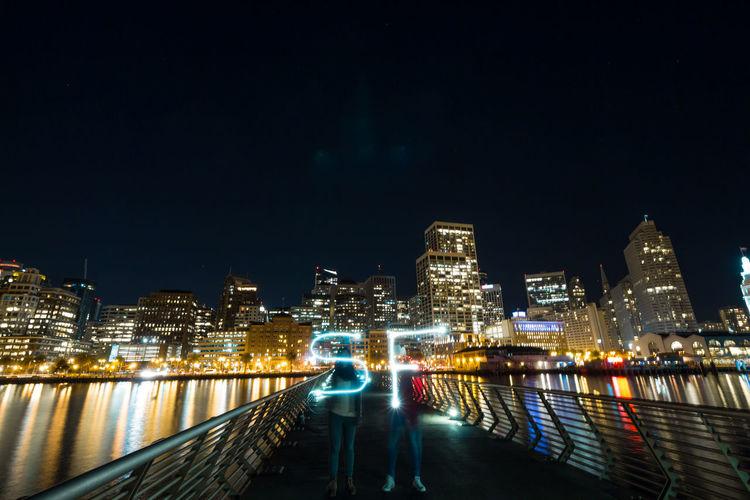 Women making light painting while standing on footbridge at night