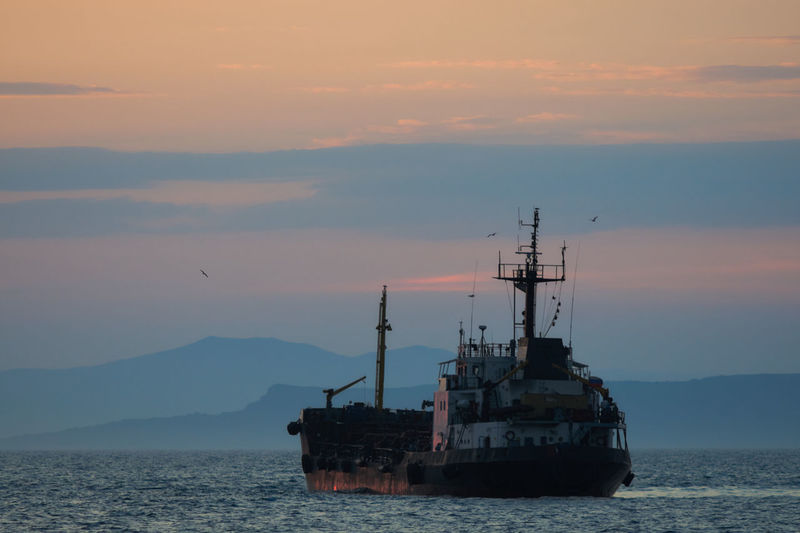 Ship sailing on sea against sky during sunset