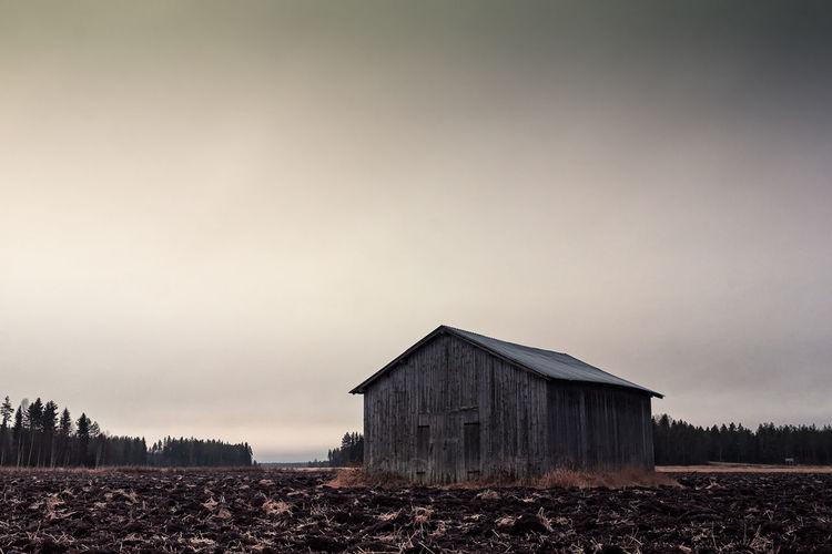 Barn on field by buildings against sky