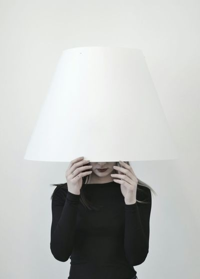 Woman wearing lamp shade while standing against white background