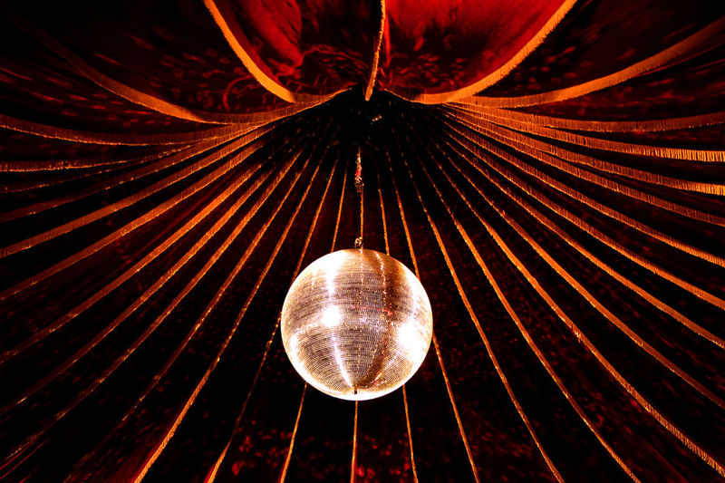 Low angle view of disco ball hanging from decorated ceiling