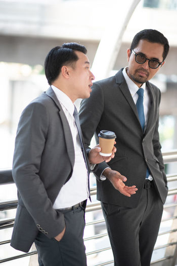 Businessmen Talking While Standing In Office