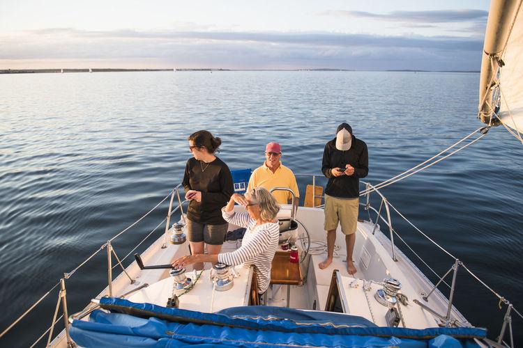 People sitting on boat in sea against sky