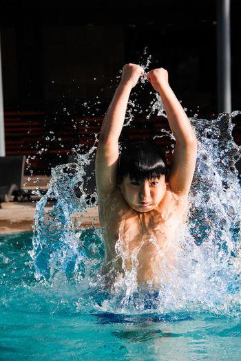 Boy splashing water in swimming pool