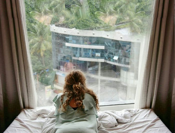 Young woman looking through window at home