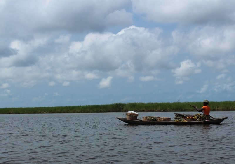 Ganvie - Local Taxi Beauty In Nature Cloud - Sky Day Leisure Activity Lifestyles Men Nature Nautical Vessel Outdoors People Real People River Scenics Sitting Sky Togetherness Tranquility Transportation Two People Vacations Water Women