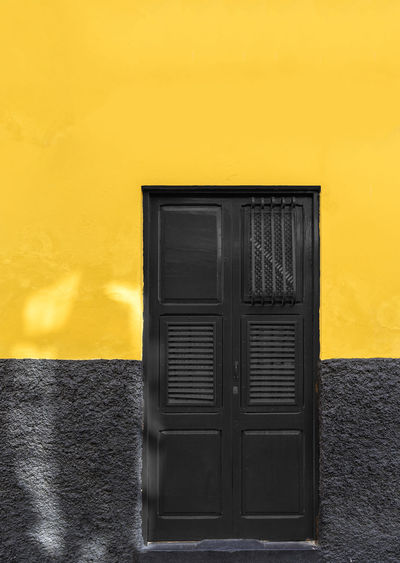 Yellow and black wall with door Architecture Black Color Building Building Exterior Built Structure Close-up Closed Day Door Entrance No People Old Outdoors Protection Safety Security Single Object Wall - Building Feature Window Yellow