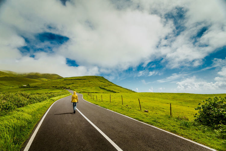 Rear view of woman walking on mountain road against cloudy sky