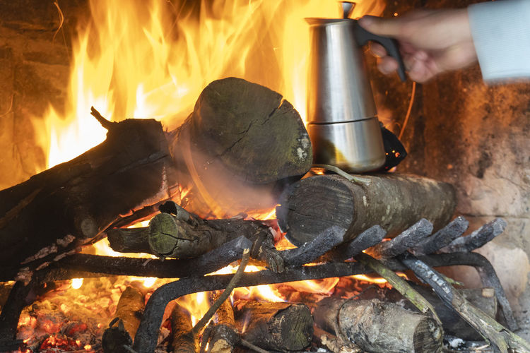 Burning Fire Heat - Temperature Flame Fire - Natural Phenomenon Wood Log Wood - Material Nature Glowing Firewood Preparation  Motion Food And Drink Food Real People Kitchen Utensil Hand Orange Color Human Hand Outdoors Bonfire Preparing Food Campfire