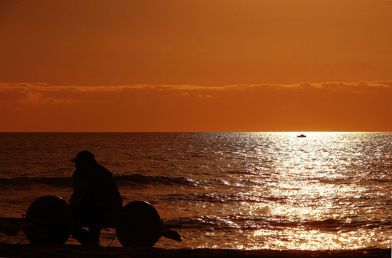 Silhouette man sitting on beach against orange sky