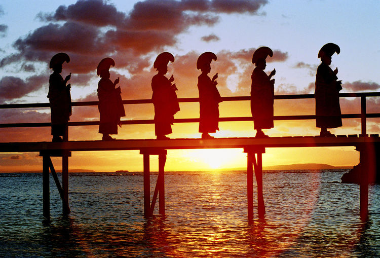 Silhouette people standing on pier over sea against sky during sunset