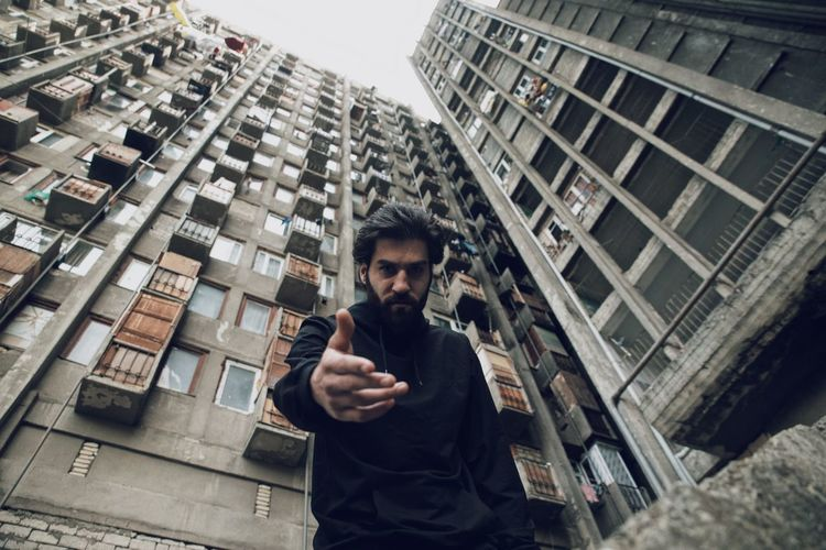 Portrait of young man using mobile phone in city
