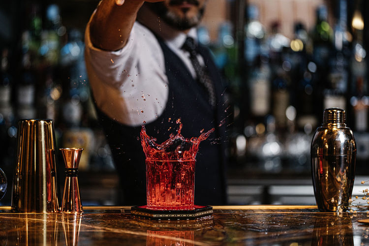 Bartender adding ice in drink at bar counter