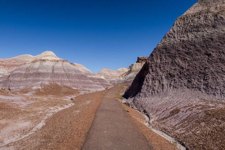 Path leading towards badland hills against clear blue sky