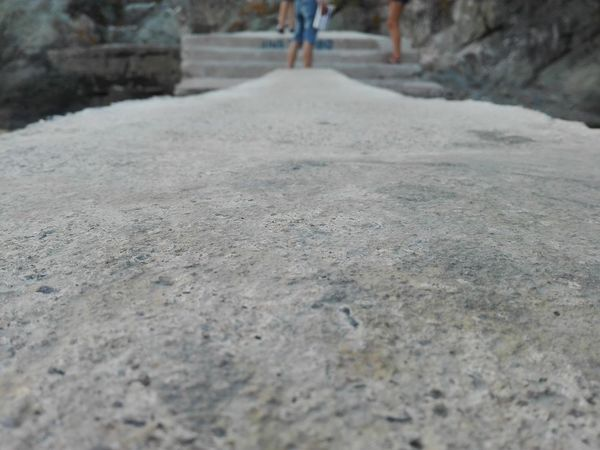 Waiting for the summer to come Blurred Background Blury Background Close-up Concrete Concrete And Rocks Day Focus Object Focus On Foreground Focused Gray Grey Legs In The Background Low Section One Person Outdoors People In The Background People In The Distance Real People Sea Side Surface Level