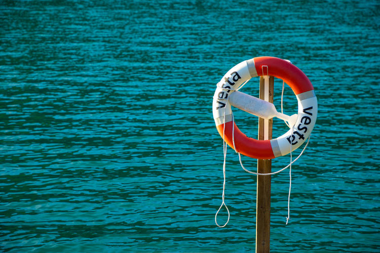 Close-up of life belt on pole by rippled sea