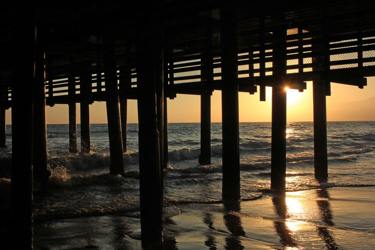 Silhouette Pier On Beach Against Sky During Sunset