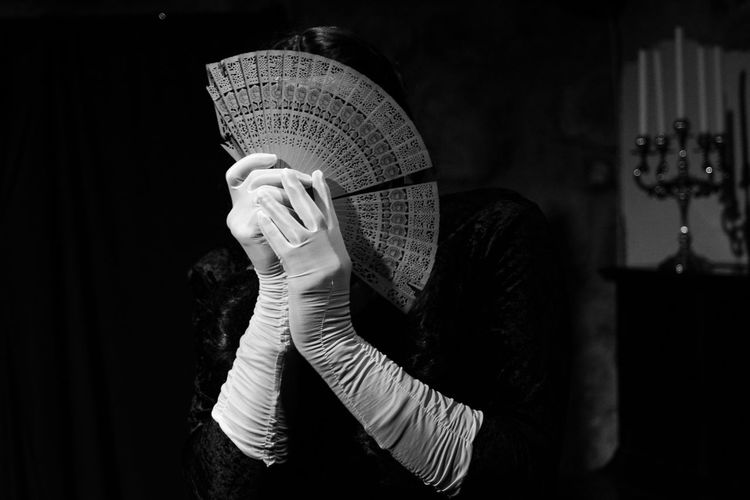 Woman face covered with hand fan in darkroom