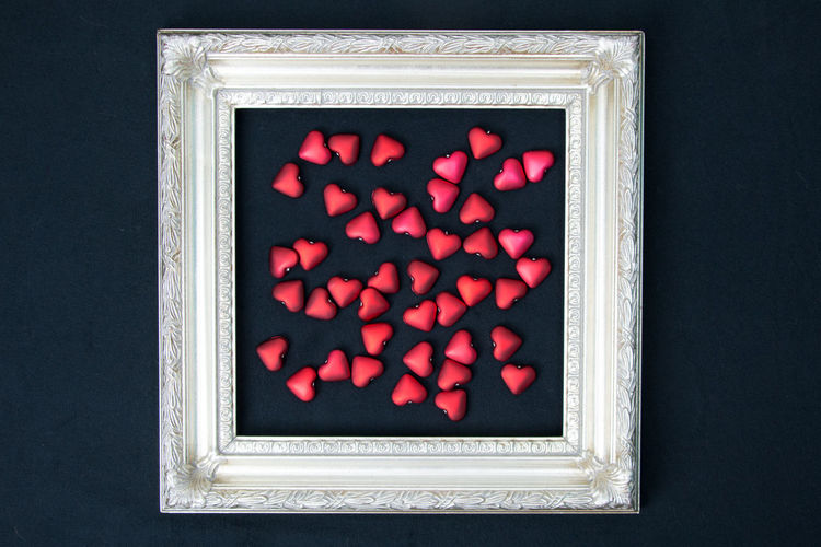 Directly above shot of red heart shapes in picture frame on black background