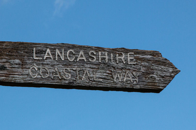 Low angle view of information sign against clear blue sky
