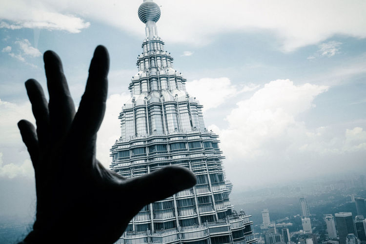 Cropped hand gesturing against petronas tower in city