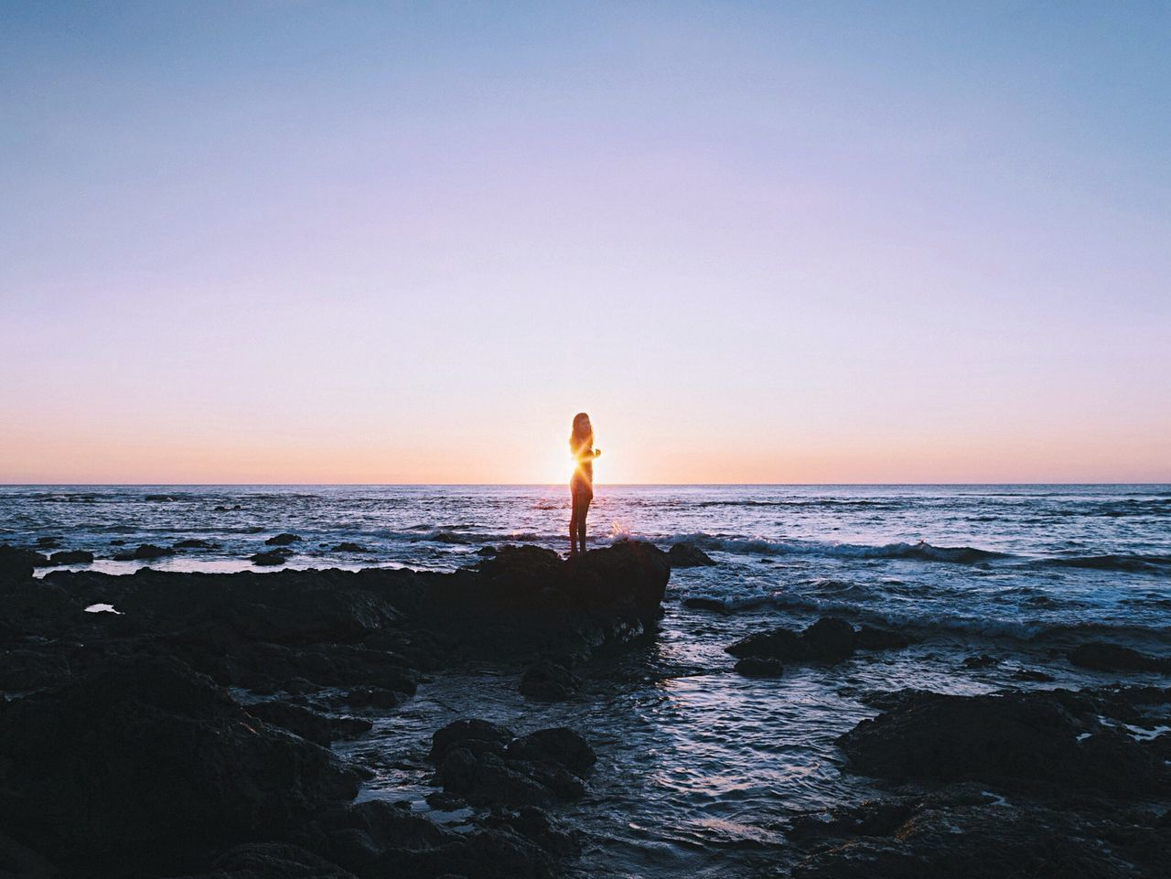 Woman standing on rock against sea during sunset