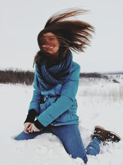 Full length of smiling young woman on beach during winter