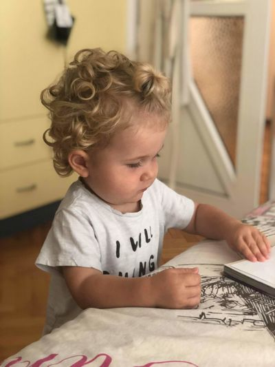 Baby boy with book at table