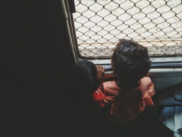 High Angle View Of Children Looking Through Window In Train