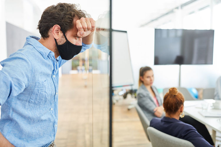 Businessman wearing mask standing against colleagues in office