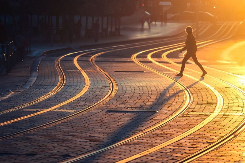 Side view of silhouette woman crossing city street during sunset