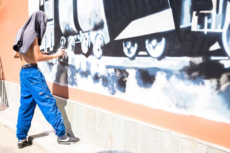 Architecture Art And Craft Blue Casual Clothing Day Graffiti Jeans Leisure Activity Lifestyles Men Nature One Person Outdoors Real People Shadow Side View Standing Sunlight Technology Wall - Building Feature