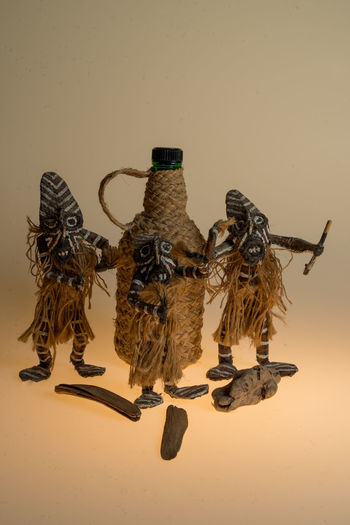 Three Afro-Brazilian Priests dancing to praise God Cachaça AFRICAN CULTURE Art And Craft Creativity Bottle Cachaça Close-up Day Dolls Indoors  No People Still Life Studio Photography Studio Shot Sunset White Background Wood - Material