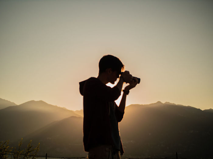 Man photographing on mountain against sky during sunset