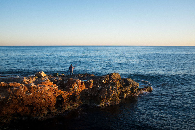Rear view of man fishing on rocky shore against clear sky