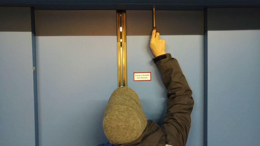 Rear View Of Man Unlocking Elevator Door
