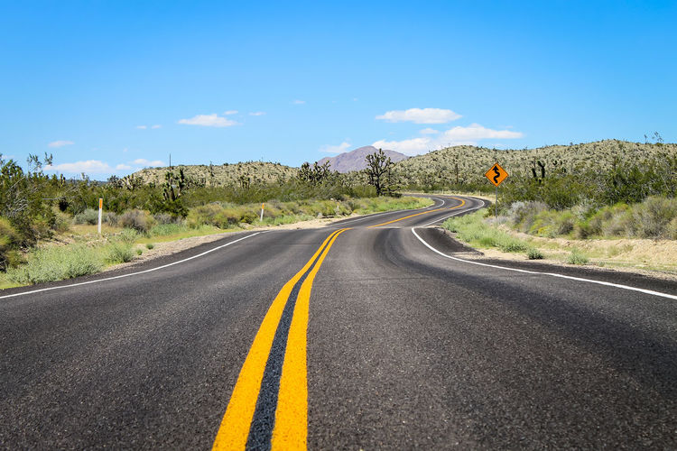 California Mojave Desert Road Country Road Dividing Line Double Yellow Line Joshua Tree Mojave National Preserve No People Pavement Road Road Marking Sign Sky The Way Forward Transportation Winding Road
