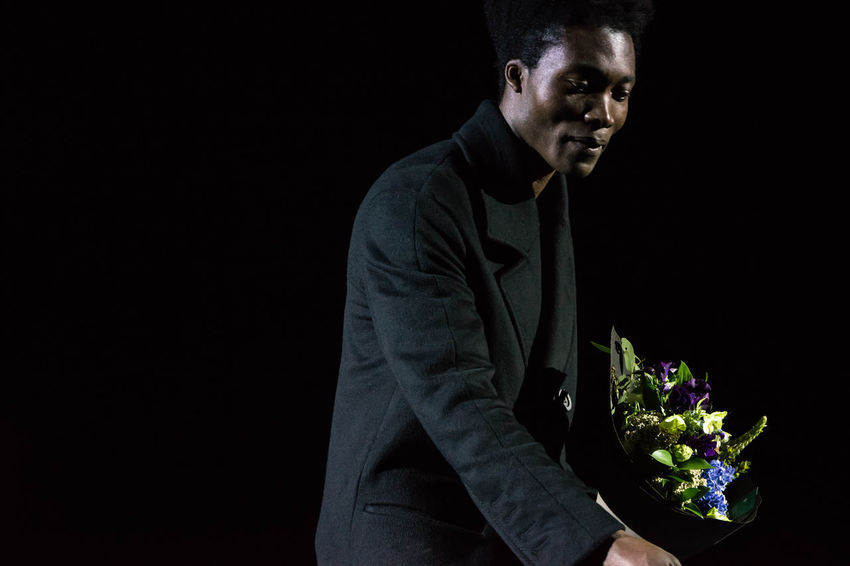 Performance of Benjamin Clementine in Kiev Ukraine Benjamin Clementine Black Background Casual Clothing Con Darkness Darkroom Flowers Performance Person Studio Shot Three Quarter Length Young Adult