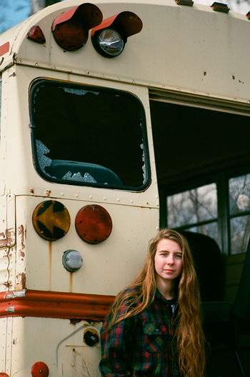 Young woman standing in front of an abandoned school bus